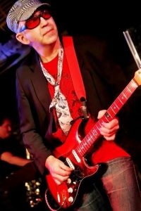 A man wearing a red shirt holding a guitar