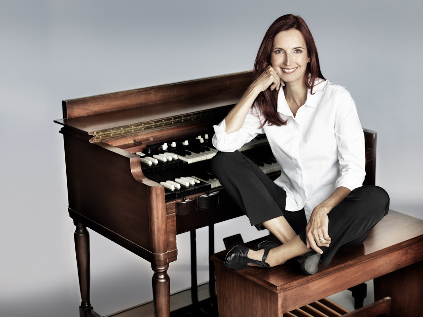 Barbara Dennerlein sitting on a piano